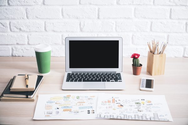 Closeup of creative hipster desktop with blank laptop screen, business sketch, coffee cup, cactus and other items on white brick wall background. Mock up